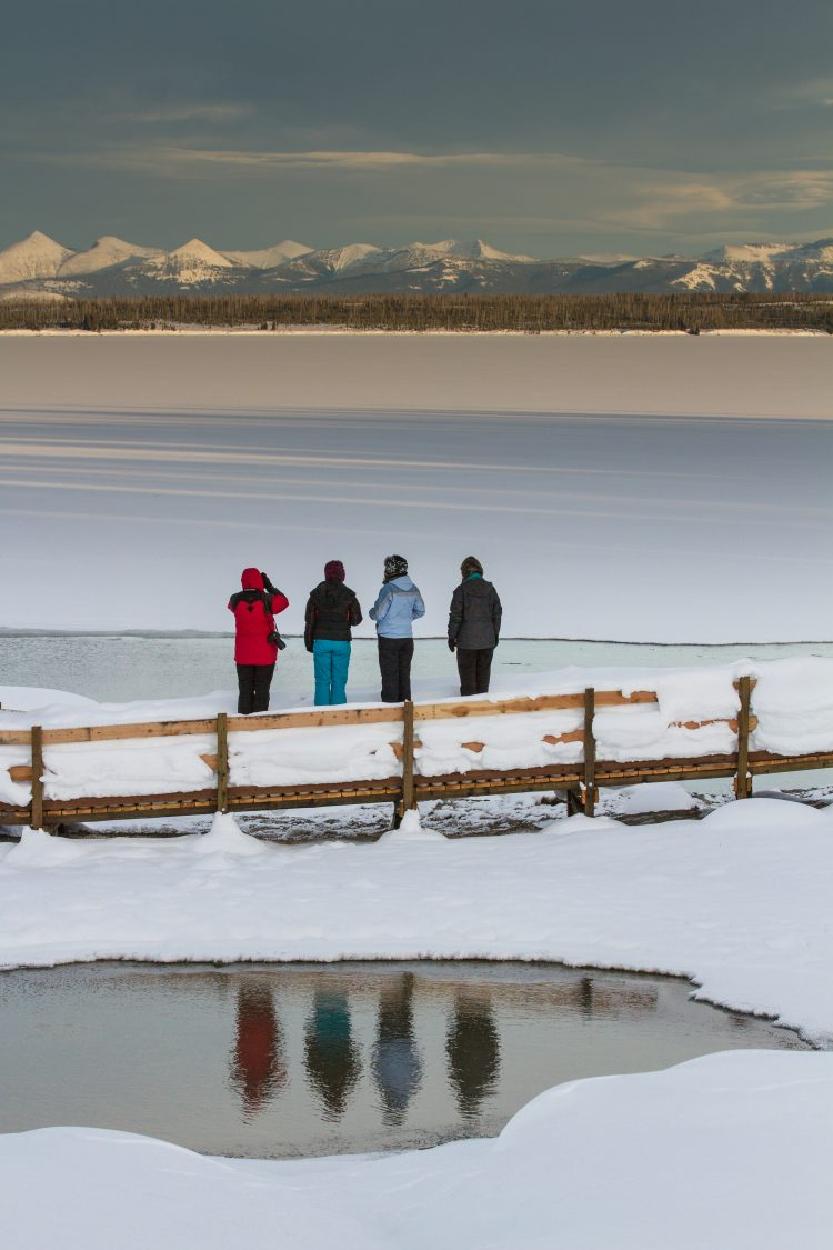4 people overlooking a frozen lake, hot spring in foreground