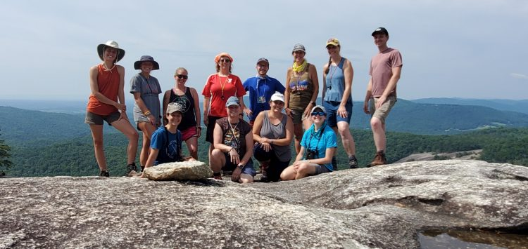12 adults standing or sitting in two rows on top of a rock face of Stone Mountain (North Carolina) overlooking the Blue Ridge Mountains