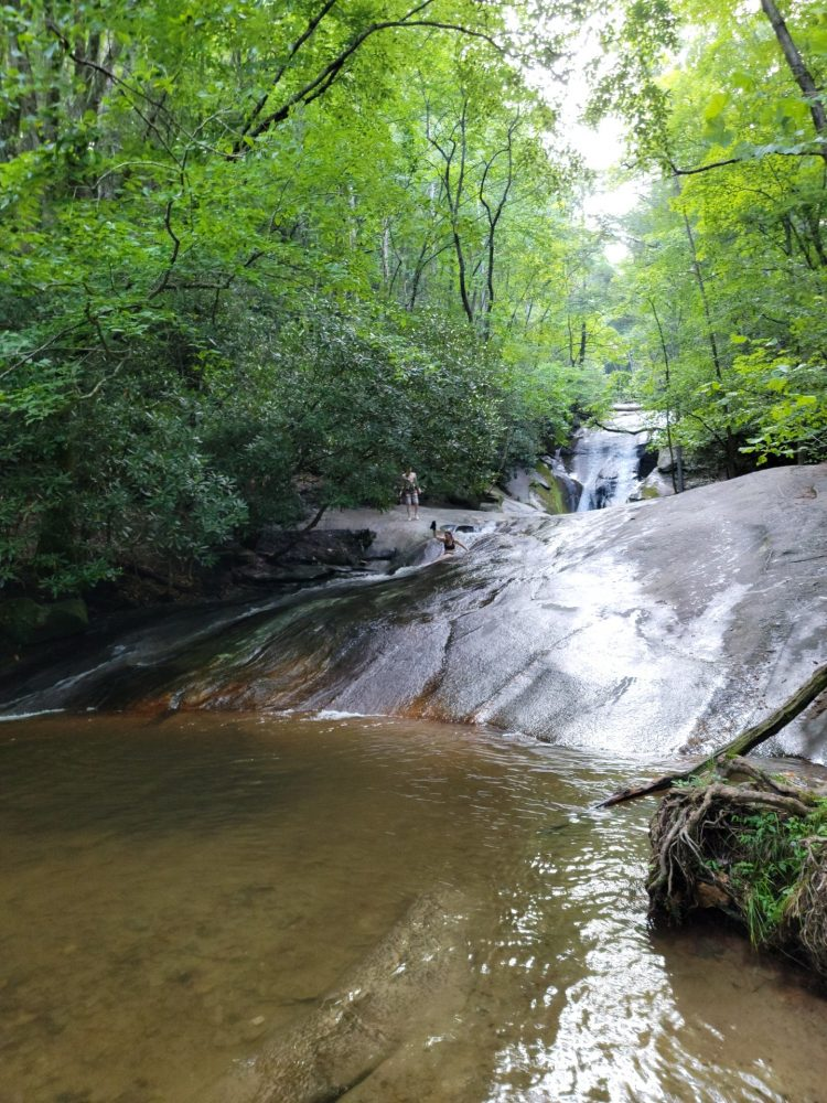 Foreground is a pool of clear water. Rocks slope upward from the pool creating a natural waterslide. A person is standing at the top of the slide, and another person is sliding down. Pine trees and rhododendron frame a waterfall and pools on either side.