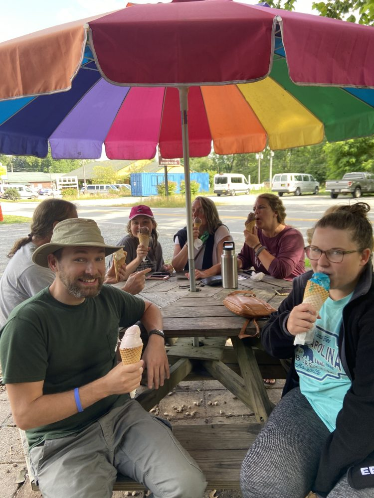 Group eating ice cream under a brightly colored umbrella.