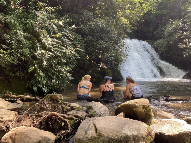 Three people sitting at the edge of a pool at the base of a waterfall.