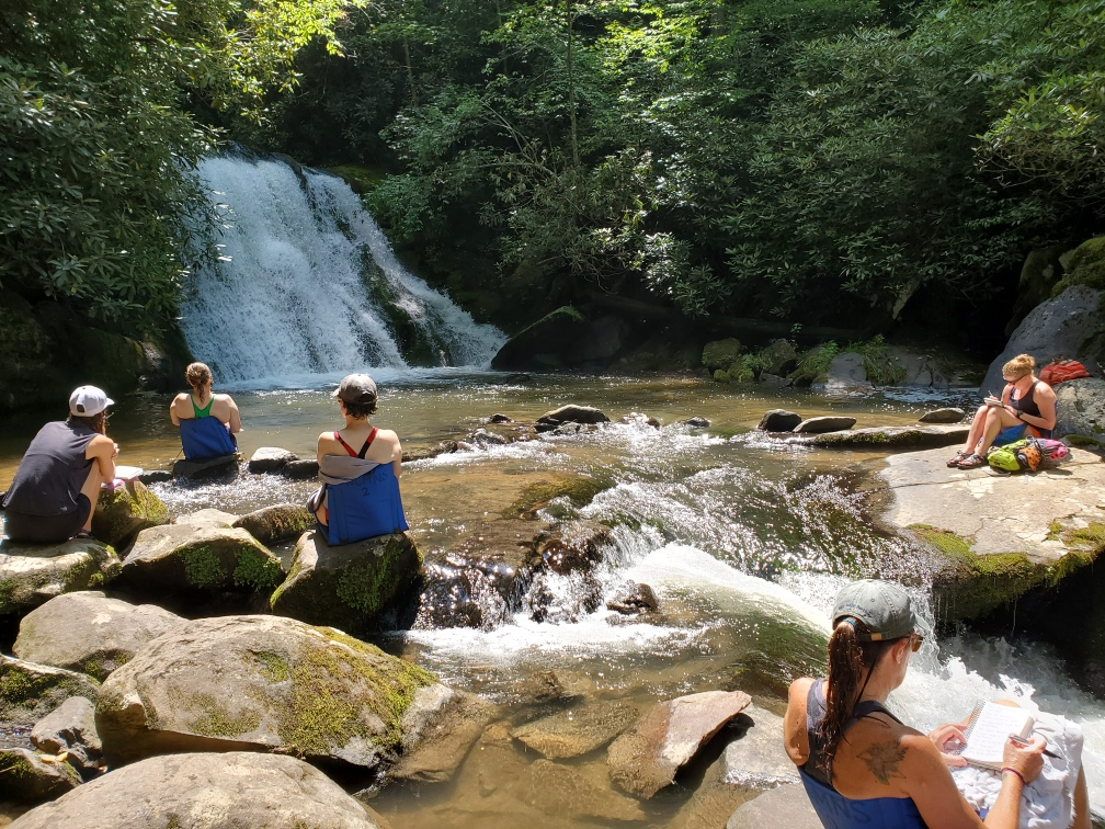 Five people sitting scattered on rocks around a pool at the base of a waterfall